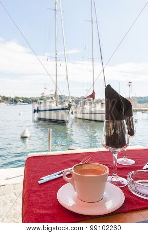 Cup of coffee on waterfront restaurant table next to harbour in Villefranche-sur-Mer on French Riviera, France.