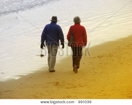 Seniors Strolling On Beach