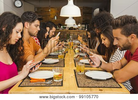 Group of friends at a restaurant with all people on the table occupied with cellphones