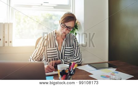 Young Businesswoman Writing Notes On Her Desk