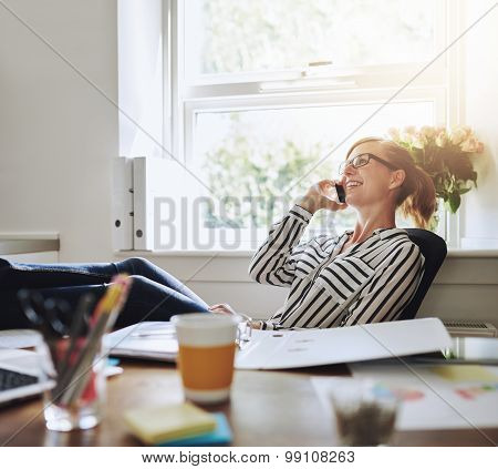 Happy Businesswoman At Her Desk Talking On Phone