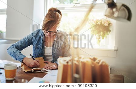Woman Writing Notes On Paper Gift Bag On The Table