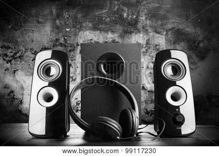 Modern black sound speakers and headphones on dark background
