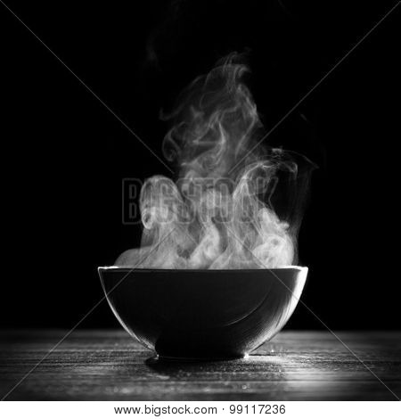 Bowl of hot soup on black background