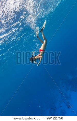 Freediver woman descends into deep blue water