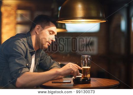 people and bad habits concept - man drinking beer and smoking and shaking off ashes of cigarette at bar or pub