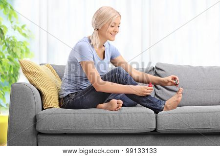 Young woman polishing her toenails and smiling seated on a gray couch at home