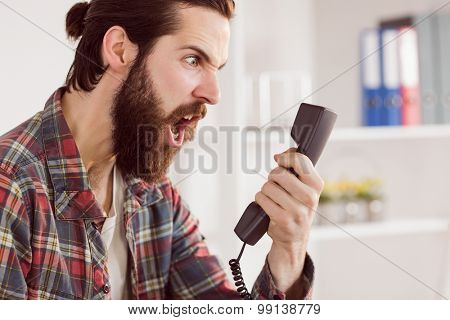 Hipster angry businessman making a call in his office