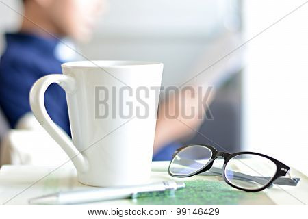 Coffee Cup, Eye Glasses & Pen Over A Book With Blur Background Of A Man Reading Book
