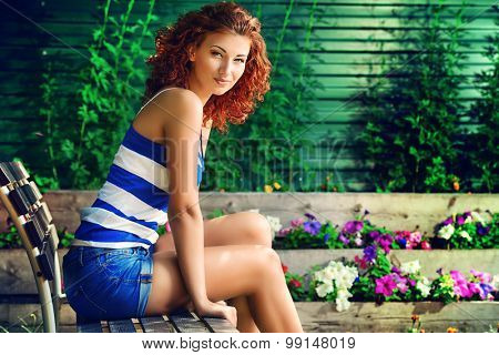 Beautiful young woman with curly foxy hair outdoors. Beauty, fashion.