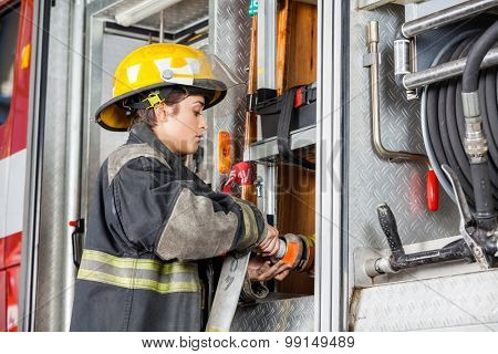 Side view of female firefighter fixing water hose in truck at fire station poster