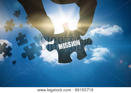 The word mission and hand holding jigsaw piece against bright blue sky with clouds