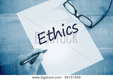 The word ethics against left hand writing on white page on working desk
