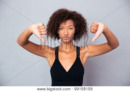 Portrait of a young african woman showing thumb down over gray background