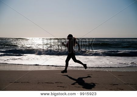 Woman running on the beach and sunrise in silhouette poster