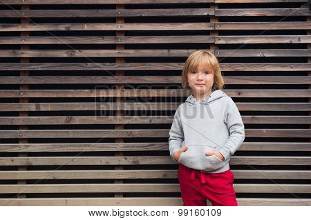 Fashion portrait of adorable toddler boy wearing grey sweatshirt and red trainings, standing against wooden background poster