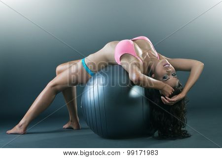 Pretty young woman in pink lingerie laying on fit ball, doing workout