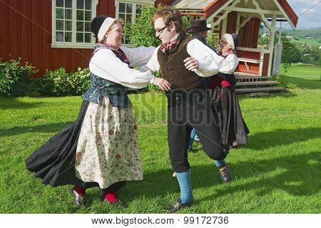 People wearing historical costumes perform traditional dance in Roli, Norway.