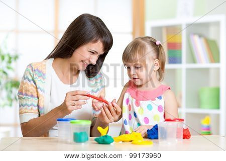 mother teaches her child to play with colorful play clay toys
