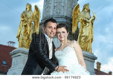 Bride And Groom Posing In Front Of Fountain