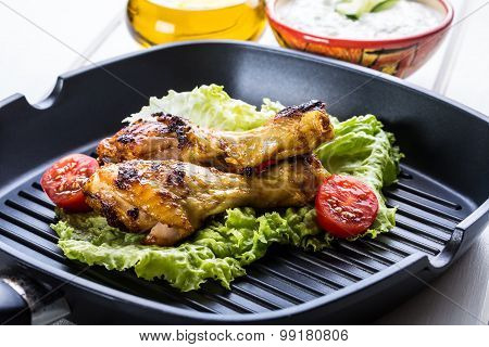 Grilling. Grilled chicken. Grilled chicken legs. Grilled chicken legs, lettuce and cherry tomatoes.