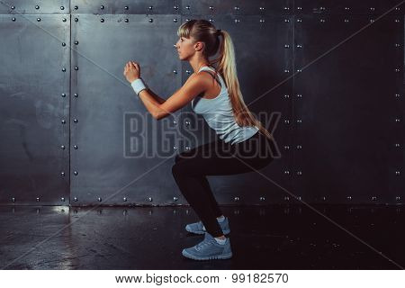 Athletic young woman fitness model warming up doing squats exercise for the buttocks concept sport s
