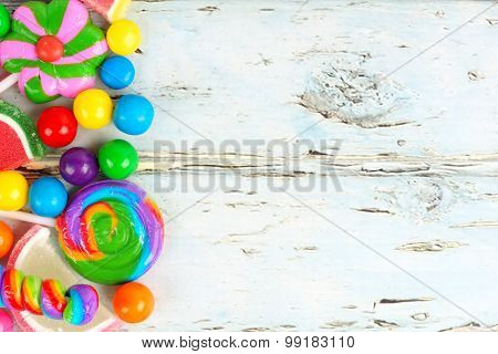 Side border of colorful candies against rustic wood