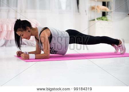 Slim fitness young woman Athlete girl doing plank exercise at home concept training workout crossfit