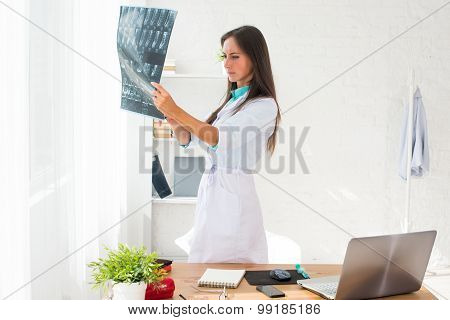 Young woman doctor watching a patient x-ray in hospital.