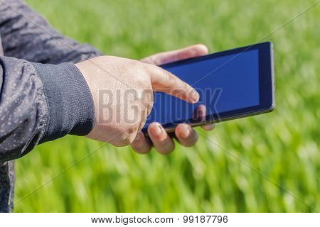 Hand with tablet PC on cereal field
