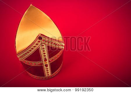 Mitre or mijter of Sinterklaas. On red background with copy space and vignette. Part of a dutch santa tradition