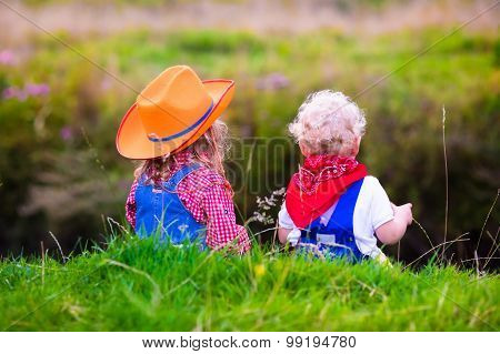 Little boy and girl dressed up as cowboy and cowgirl playing with toy rocking horse in park.