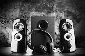 Modern black sound speakers and headphones on dark background poster