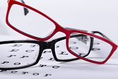 two reading red and black eyeglasses and eye chart close-up on a light background poster