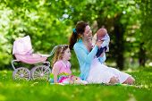 Family with children enjoying picnic outdoors. Mother with newborn baby and toddler child relax in a park. Little girl playing with toy stroller. Mom and kid play with infant boy. Kids birthday party. poster
