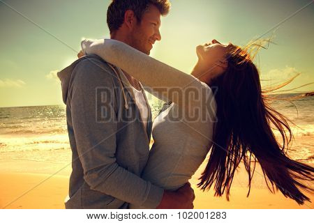 embracing dancing carefree couple on beach