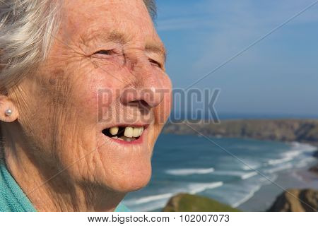 Happy elderly lady pensioner with dental problems and a tooth missing by beautiful coastal scene
