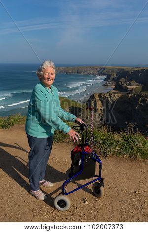 Elderly lady pensioner with three wheel mobility aid by beautiful coast scene