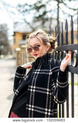 Atractive Girl In Black Coat And Sunglasses Standing Near A Wrought Iron Fence