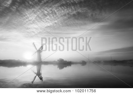 Stunning Landscape Of Windmill And River At Dawn In Black And White