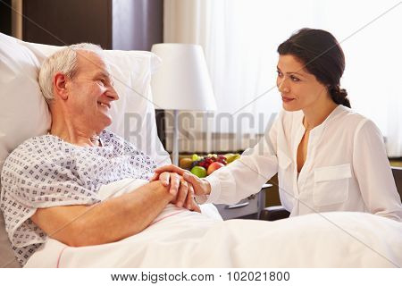 Female Doctor Talking To Senior Male Patient In Hospital Bed