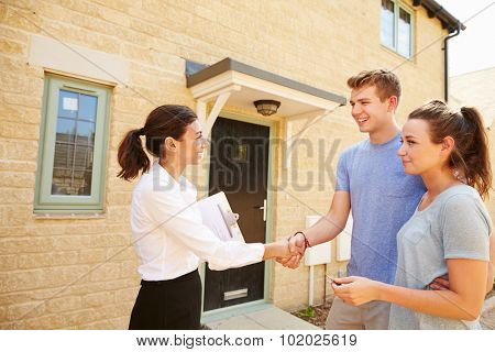 Real estate agent shaking hands with new property owners