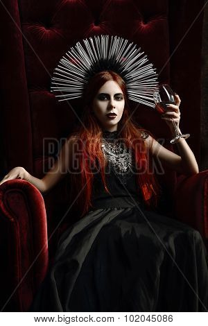 Gothic Fashion: Young Woman Sitting In Chair And Holding Glass Of Wine