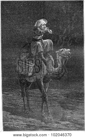 The author blowing on the tinder to light his compass in the desert, vintage engraved illustration. Le Tour du Monde, Travel Journal, (1865).