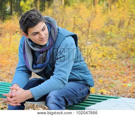 Young smiling man portrait sitting in autumn park on a bench.