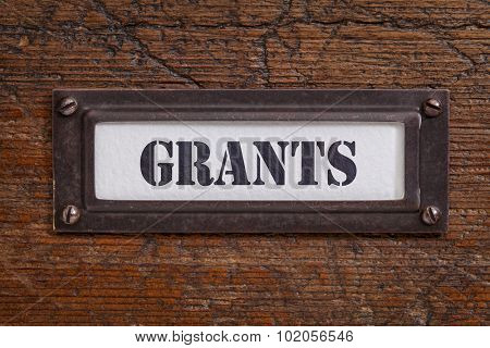 grants  - file cabinet label, bronze holder against grunge and scratched wood, financial concept