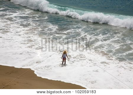 Unidentifiable people frolic in the surf of the Pacific Ocean in Laguna Beach California. Laguna Beach in Southern California a world wide tourist destination. Everyone Loves the beach and the ocean