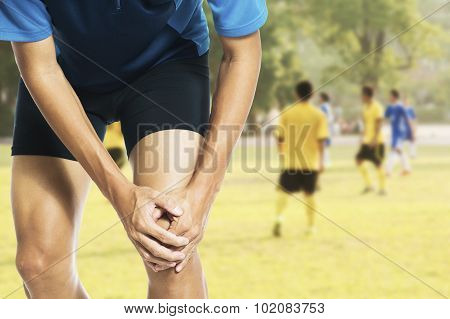 Male athlete runner touching foot in pain due to sprained ankle poster