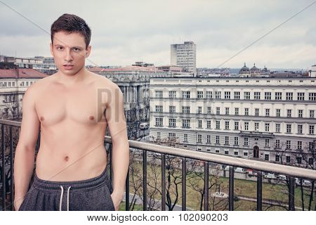 Shirtles Handsome Young Man In Sweatpants Standing On Terrace