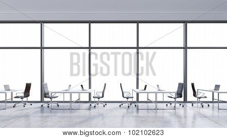 Workplaces In A Modern Panoramic Office, Copy Space In The Windows. Open Space. White Tables And Bla